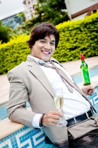 Young cheerful Indian businessman relaxing at swimming pool side (Little Soft Image)