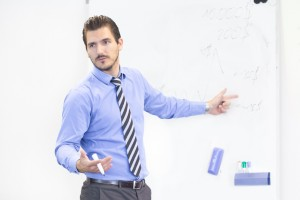Business man making a presentation in front of whiteboard. Business executive delivering a presentation to his colleagues during meeting or in-house business training, explaining business plans.