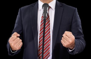 Cropped view of a man in a suit speaking into a microphone with his hands in fists
