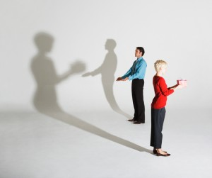 Businessman and woman standing so shadows look like she's giving him a gift